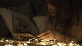 Una madre joven mirar un álbum de foto de familia en casa en el sofá almacen de metraje de vídeo