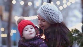 Una madre joven que abraza con su pequeña hija que la detiene y que mira chispas Una familia feliz luces encendido almacen de video