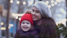 Una madre joven que abraza con su pequeña hija que se sienta en un banco y que mira la cámara Una familia feliz luces encendido almacen de video