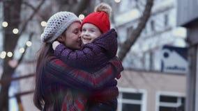 Una madre joven que juega y que abraza con su pequeña hija al aire libre, deteniendo a la hija en sus manos Una familia feliz metrajes