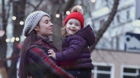 Una madre joven que juega y que abraza con su pequeña hija al aire libre, deteniendo a la hija en sus manos Una familia feliz almacen de video
