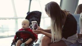 Una madre joven toma una imagen de su pequeño hijo en un cochecito de niño en un teléfono celular almacen de metraje de vídeo