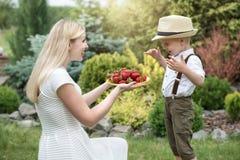 Una madre joven trata sus fresas fragantes maduras del hijo del beb? foto de archivo libre de regalías