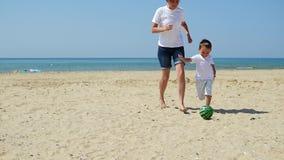 Una madre joven y su niño están jugando una bola en una playa arenosa La familia feliz está jugando a fútbol r almacen de metraje de vídeo