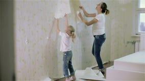 Una madre joven y una hija que quitan el papel pintado almacen de metraje de vídeo