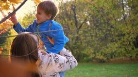 Una madre juega con un niño, lo sostiene en los brazos, lo arroja. Los rayos del sol a través del niño. La risa y la alegría d almacen de metraje de vídeo