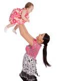 Una madre lanza a su niño infantil en el aire Fotos de archivo