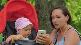 Una madre mostra un telefono cellulare ad un bambino in un passeggiatore stock footage