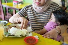 Una madre que goza comiendo el almuerzo mientras que lleve a una hija del sueño en su brazo fotografía de archivo