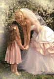 Una madre rubia hermosa con una pequeña muchacha de la hija que se acurruca en el fondo de la naturaleza de flores verdes y púrpu Imágenes de archivo libres de regalías