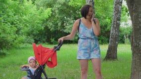 Una madre sacude a un niño en una silla de ruedas y habla en su teléfono metrajes