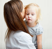 Una madre sta tenendo una ragazza ammalata. fotografia stock