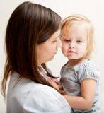 Una madre sta tenendo una ragazza ammalata. fotografia stock libera da diritti