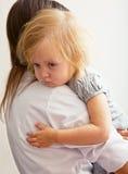 Una madre sta tenendo una ragazza ammalata. immagini stock libere da diritti