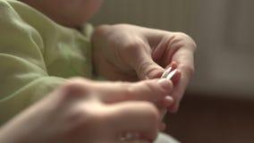 Una madre taglia le unghie di un bambino stock footage