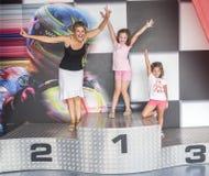 Una madre y sus hijas en un podio de la competencia Foto de archivo