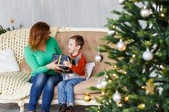 Una madre y un hijo con los regalos de Navidad delante del piel-árbol con las velas Imagen de archivo