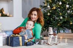 Una madre y un hijo con los regalos de Navidad delante del piel-árbol con las velas Fotografía de archivo