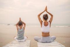 Una madre y un hijo est?n haciendo ejercicios de la yoga en la costa del oc?ano tropical fotografía de archivo
