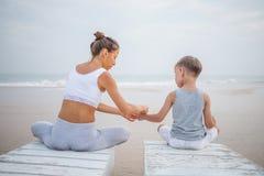 Una madre y un hijo est?n haciendo ejercicios de la yoga en la costa del oc?ano tropical imagen de archivo