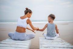 Una madre y un hijo est?n haciendo ejercicios de la yoga en la costa del oc?ano tropical foto de archivo libre de regalías