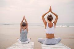 Una madre y un hijo est?n haciendo ejercicios de la yoga en la costa del oc?ano tropical fotografía de archivo libre de regalías