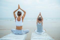 Una madre y un hijo est?n haciendo ejercicios de la yoga en la costa del oc?ano tropical imagen de archivo libre de regalías