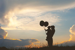 Una madre y un hijo que juegan al aire libre en la silueta de la puesta del sol Fotos de archivo libres de regalías