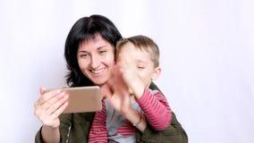 Una madre y un niño jovenes felices están mirando la pantalla de un smartphone y están agitando sus manos mientras que comunica e almacen de metraje de vídeo
