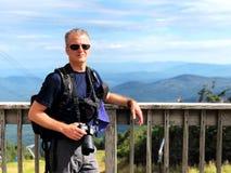 Una magra dell'uomo contro un'inferriata con il fondo della cresta della montagna fotografia stock libera da diritti