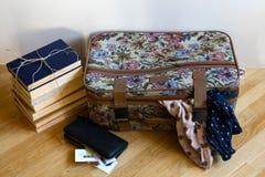 Una maleta coloreada para un viaje, con dos bufandas pegándose fuera de él, fotografía de archivo libre de regalías