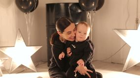 Una mamá feliz joven está jugando con su muchacho de un año en un estudio con las estrellas metrajes
