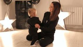 Una mamá feliz joven está jugando con su muchacho de un año en un estudio con las estrellas almacen de metraje de vídeo