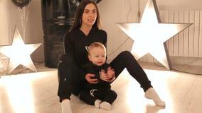 Una mamá feliz joven está jugando con su muchacho de un año en un estudio con las estrellas almacen de video