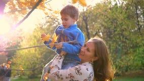 Una mamá juega con un niño, lo sostiene en los brazos, lo arroja. Los rayos del sol a través del niño. La risa y la alegría d almacen de video