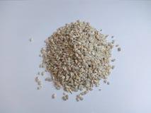 Una manciata di grani dell'orzo su un fondo bianco Fotografia Stock