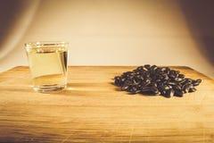 Una manciata di seme di girasole, olio di girasole in un vetro sulla tavola Vista laterale fotografie stock libere da diritti