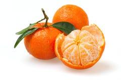 Una mandarina pelada y dos con una cáscara Imagenes de archivo