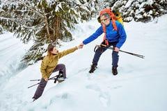 Una mano amiga alta para arriba en las montañas en el alza del invierno Imágenes de archivo libres de regalías