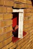 Una mano apre una finestra. Immagine Stock