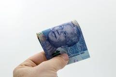 Una mano caucásica que lleva a cabo cientos notas surafricanas doblada del rand con un fondo llano imagen de archivo libre de regalías