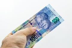 Una mano caucásica que lleva a cabo nota surafricana de cientos randes con un fondo llano fotografía de archivo