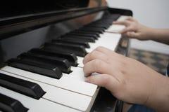 Una mano che gioca con il fondo della tastiera di piano con il fuoco selettivo Immagine tonificata colore normale fotografie stock libere da diritti