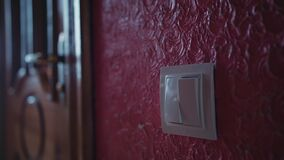 Una mano che gira in funzione e a riposo un interruttore della luce in una casa archivi video