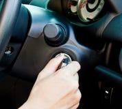 Una mano che gira un tasto dell'automobile Immagini Stock Libere da Diritti