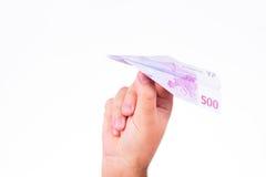 Una mano che giudica un aereo di carta fatto con una nota dell'euro 500 Fotografia Stock