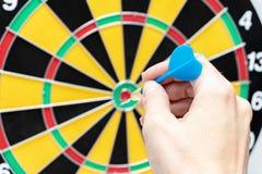 Una mano che giudica un dardo blu pronto a gettarlo ad un obiettivo, ad una strategia e ad un'abilit? del bersaglio nel concetto  immagine stock