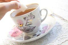 Una mano che mette uno zucchero in una tazza Immagine Stock Libera da Diritti