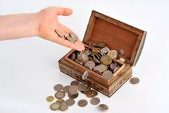 Una mano che si muove verso un caso con le monete Immagini Stock