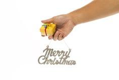 Una mano che tengono il contenitore di regalo giallo ed il Buon Natale firmano immagine stock libera da diritti